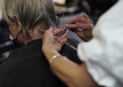 Stylist cutting the hair of male customer